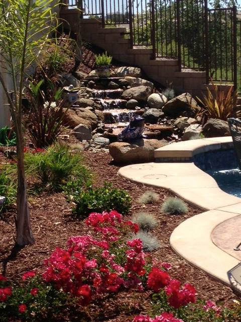 Waterfall feature continually runs, softening this tropical Temecula yard.