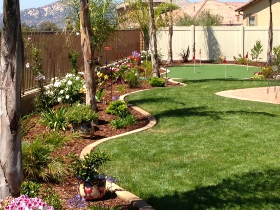 Backyard of residence incorporating hardscape, lawn, and putting green in Temecula, CA