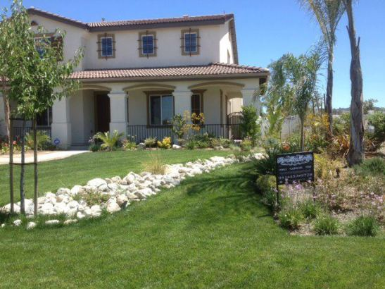 Aloha Landscape placed  stone river in the front of this gorgeous home.