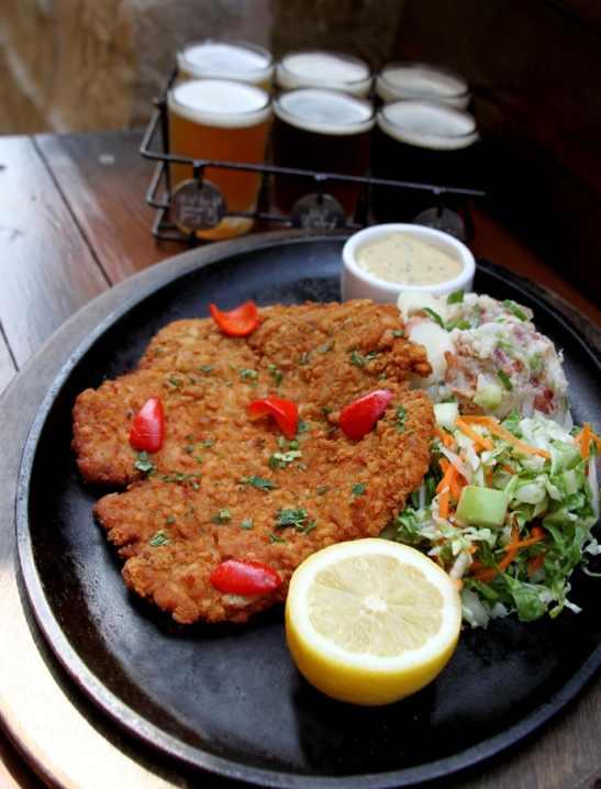 Pretzel crusted schnitzel, paired with Napa cabbage slaw and authentic German potato salad
