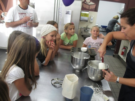 Rapt bakers in training learn to fold cupcake batter together